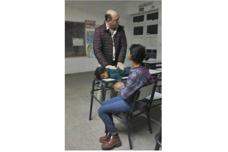 Alejandra escuchca atentamente a su profesor mientras su pequeño duerme.
