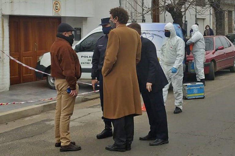 Los fiscales y autoridades policlaes frente a la casa del crimen